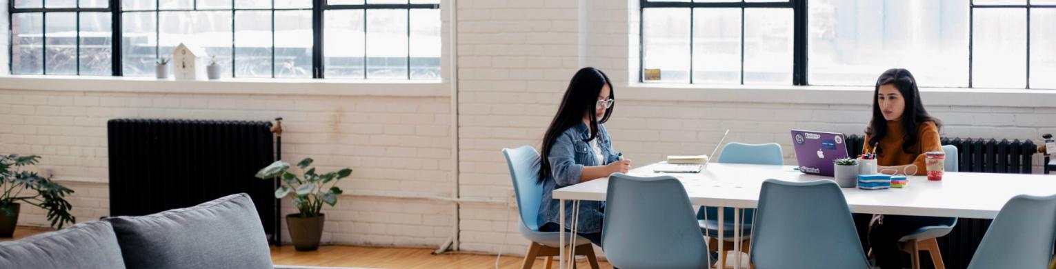 two-women-sitting-on-a-desk